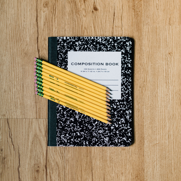 composition notebook with pencils