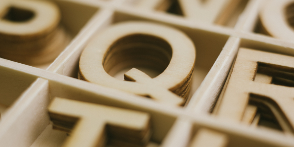 wooden letters in boxes. Letter Q is in focus
